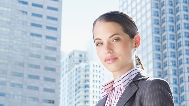 Women in business attire with city buildings in background, getty images