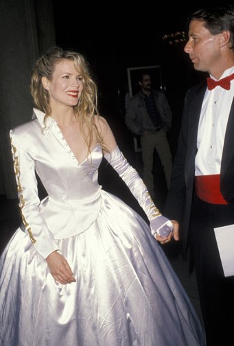 Kim Basinger in a white ball gown and matching one-armed jacket in 1990.