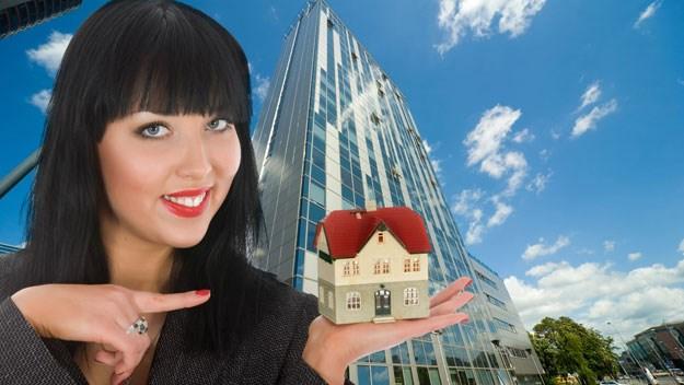 Woman holding mini house, thinkstock